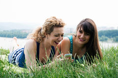 Two best girl friends laying on the grass Royalty Free Stock Photos