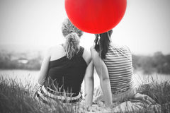 Two best girl friends sitting on the grass. Two best girl friends sitting on a blanket on the grass with big red balloon enjoying summer time, selective color Royalty Free Stock Images