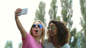 Two best girlfriends making dance moves, taking funny selfies with smartphone. Stock footage stock video