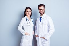 Two best smart professional smiling doctors workers in white coats holding their hands in pockets and together standing against g. Ray background stock photography