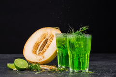 Two beverages and a melon on a black background. The green cocktails with lime and tarragon. Healthy, sweet and tasty drinks. Copy royalty free stock images