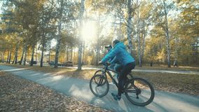 Two bicycle. Couple on bikes. Romantic biking in the autumn forest. Man and woman in similar blue coats. Man and woman riding bikes. Active family leisure stock footage