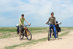 Two bicycle tourists standing on road Stock Images
