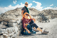 Two bicycle travelers rest on mountain road Stock Photo