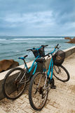 Two bicycles. On road along ocean Stock Photos