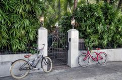 Two Bicycles and a Gate. Two bicycles flank a gate to a private garden in Key West, Florida stock photography