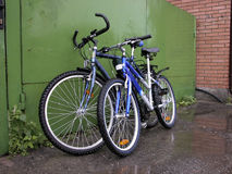 Two bicycles at green gate. And brick wall Royalty Free Stock Photography
