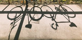 Two bicycles lean against a fence and cast a shadow silhouette on the ground stock photography