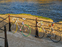 Two bicycles lean on a railing by the river Stock Images