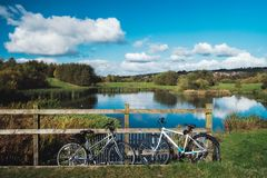 Two bicycles parking near the fence opposite the picturesque lake royalty free stock photos