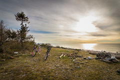 Two bicycles standing on the grass in front of the pebble shore, Jomfruland National Park, Kragero, Norway Royalty Free Stock Photography