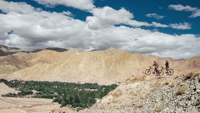 Two bicyclist traveler stay on mountain top Stock Photography
