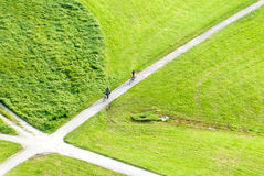 Two bicyclists approach a juncture in a green field Royalty Free Stock Photos