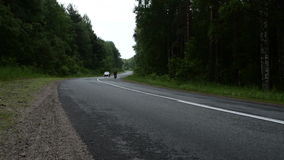 Two bicyclists and a lonely car in a forest road. Karelia stock footage