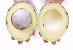 Two big avocado halves. Closeup of person holding two big halves of Mexican avocado with seed over white background Royalty Free Stock Photography