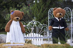 Two big bear dolls. Stand together in the garden royalty free stock photography