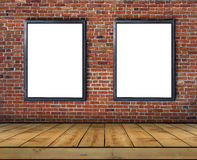 Two big blank billboard attached to a brick wall inside with wooden floor Royalty Free Stock Images