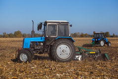 Two big blue tractor plowing a field and remove the remains of previously mown corn. Stock Image