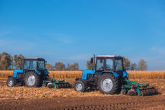 Two big blue tractor plowing a field and remove the remains of previously mown corn. Stock Images