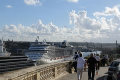 Two big cruise-ships in the harbour of Valetta on Malta Island. Tourists walking above two big cruise-ships in the harbour of Valetta on Malta Island Stock Photography