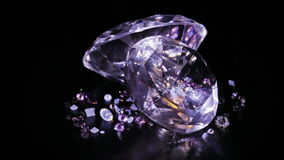 Two big diamond stones with many small one rotating. Over dark background stock footage