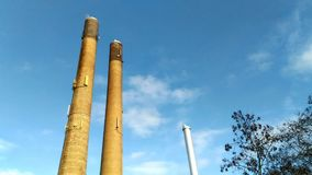 Two big factory towers. Concept of fossil fuels, global warming, manufacturing and industrial work Royalty Free Stock Photography