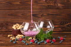 Two big glasses with fruit juice, bilberries, raspberries, peanuts in a bowl, mint on a dark brown wooden background. Royalty Free Stock Photo