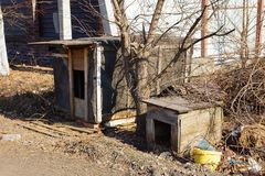 Two big gray empty doghouse on the street. In the yard royalty free stock images
