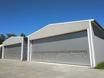 Two big industrial metal hangar or warehouse with closed doors. Metal garage building for manufacturing usage. Two big industrial metal hangar or warehouse with royalty free stock image
