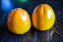 Two sharon fruits on the wooden table stock photos