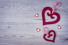 Two big red hearts with a bow and three little hearts. On a wood background stock images