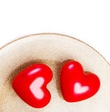 Two Big Red hearts on a golden plate isolated on white with fest Stock Photo