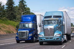 Two big rigs semi trucks in blue tone and different models with. Two big rigs semi trucks in blue tone and different styles and models with semi trailers driving Stock Image