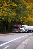 Two big rigs semi trucks with trailers on autumn road with yello Stock Photos
