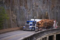 Two big rigs semi trucks transporting cargo moving towards each. Two different models of classic big rigs semi trucks transporting logs and another commercial Stock Photography