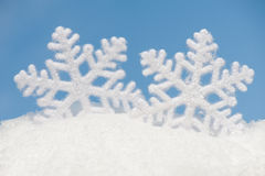 Two big snowflakes in snow against sky Stock Photos