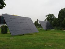 Two big solar panels. Two solar panels standing in the grass to give power on a big buiding Stock Photo