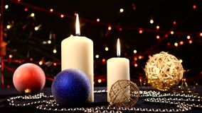 Two big white candles with balls for christmas on. Two big white candles with christmas decorations - balls, red, blue and gold on black background, bokeh, light stock footage