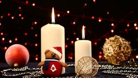Two big white candles with balls and teddy for. Two big white candles with christmas decorations - balls, red, blue and gold and teddy on black background, bokeh stock footage