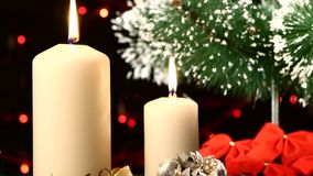 Two big white candles with christmas decorations. Two big big white candles with christmas decorations like red bow, balls and tree on black background, bokeh stock video footage