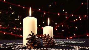 Two big white candles with pine cone for christmas stock footage