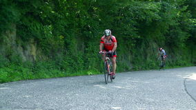Two bikers cycling uphill. VRHNIKA, SLOVENIA - JUNE 2014: Bicycle marathon competition around Vrhnika. Two bikers persistently cycling uphill in a nice scenery stock video
