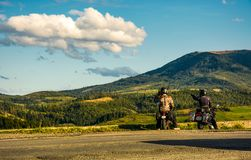 Two bikers enjoying sunset in mountains. Volovets, Ukraine - SEPTEMBER 15, 2017: two bikers on the side road enjoying beautiful sunset in mountainous landscape Stock Photo