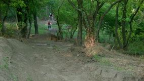 Two bikers go downhill. And pass near camera stock video footage