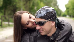 Two bikers in leather jackets on a motorcycle. Close-up of loving couple in leather jackets and bandana sitting on a motorcycle stock footage