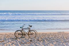 Two bikes on beach against ocean waves royalty free stock photos