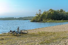 Two bikes on the beach. The sandy shoreline of the lake. stock photography