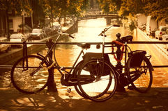 Two bikes on a canal in Amsterdam. Two bicycles on a little bridge over a canal in Amsterdam, Netherlands Royalty Free Stock Images
