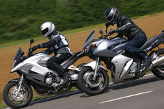 Two bikes cruising. Two all round motorbikes cruising by at high speed Royalty Free Stock Images