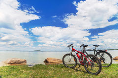Two bikes are on the picturesque background  with sky, water, grass. Stock Photos